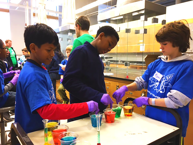 Boys conduct chemisty experiment in a lab.