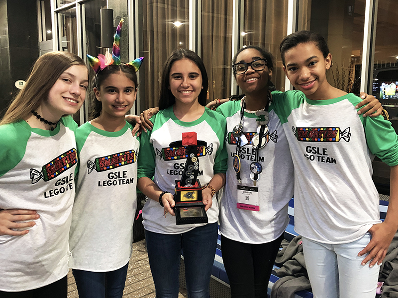 Girl Scouts pose with trophy from robotics competition.